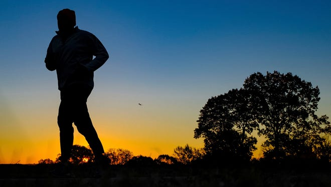 FILE - In this Tuesday, Nov. 22, 2016 file photo, a runner is silhouetted against the sunrise on his early morning workout near Arlington National Cemetery in Arlington, Va., across the Potomac River from the nation's capital. Research released on Monday, Jan. 9, 2017 suggests that people who pack their workouts into one or two days a week lower their risk of dying as much as those who exercise more often, as long as they get enough of it.