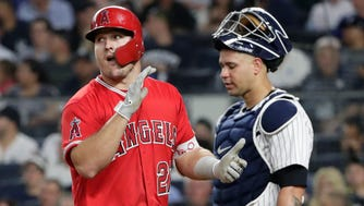 Los Angeles Angels' Mike Trout (27) walks past New York Yankees catcher Gary Sanchez after scoring on his home run during the fifth inning of a baseball game Friday, May 25, 2018, in New York.