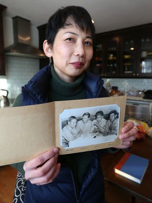 Julie Shiroishi, at her Beacon home Feb. 13, 2017, holds up a photo of her father, Tom Shiroishi, taken after he enlisted in the army during World War II . Before he enlisted, he was in an internment camp for Japanese-Americans in California.