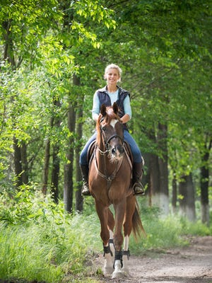 Young woman riding a horse through woodland
