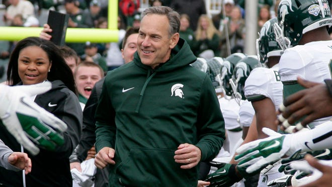 Michigan State football coach Mark Dantonio leads a group of students onto the field before the spring game April 25, 2015, in East Lansing.