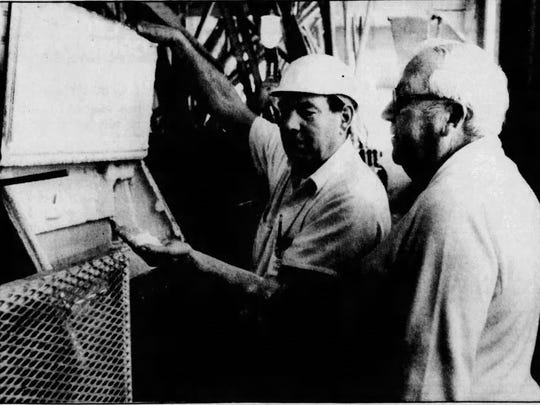 Cereal Foods plant manager Del Hollern looks on as milling superintendent Al Brown holds partially processed flour at the Montana Flor Mills building in 1986.