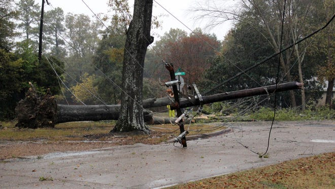A utility pole lies across a street in north Greenwood, Miss., after it was knocked down by during a thunderstorm Monday, Nov. 28, 2016. More storms are forecast for Mississippi on Tuesday night.