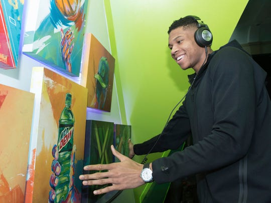 Giannis Antetokounmpo interacts with music murals at Mountain Dew Courtside HQ at New Orleans Board of Trade during NBA All-Star 2017 on Friday,.