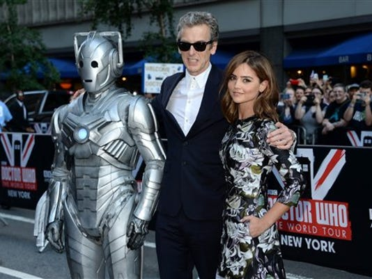 "Actors Peter Capaldi and Jenna Coleman pose with Cyberman at the BBC America's ""Doctor Who"" premiere fan screening at the Ziegfeld Theatre on Thursday, Aug. 14, 2014, in New York. (Photo by Evan Agostini/Invision/AP)"