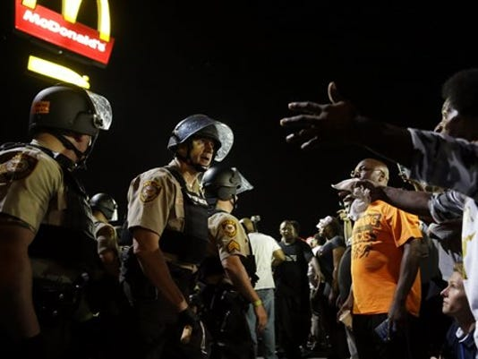 Officers and protesters face off along West Florissant Avenue, Monday, Aug. 10, 2015, in Ferguson, Mo. Ferguson was a community on edge again Monday, a day after a protest marking the anniversary of Michael Brown's death was punctuated with gunshots.