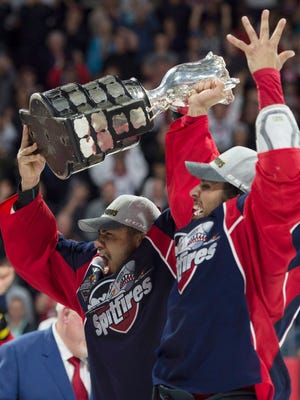 Windsor Spitfires left wing Jeremiah Addison, left, and defenseman Jalen Chatfield raise the trophy after defeating the Erie Otters to win the Memorial Cup in Windsor, Ontario, on May 28, 2017.