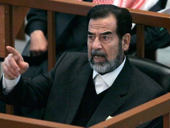 Ousted Iraqi President Saddam Hussein reacts in court