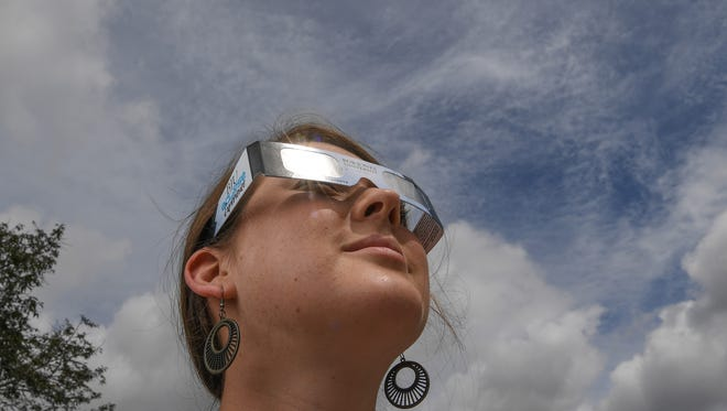 Abby White of Bob Jones University tries out a pair of the eclipse shades with the school name on them, as the sun breaks through clouds in Greenville on Wednesday.   The school is ready to host a Solar Eclipse viewing on August 21 at the school, with their name, safety instruction, and their website on the paper part of the viewing goggles.