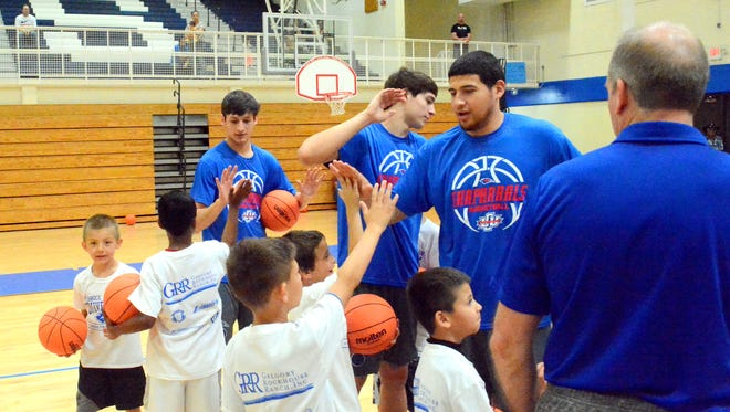 Local youngsters in grades one through four exchange high fives with Lubbock Christian basketball players toward the end of Saturday's camp.