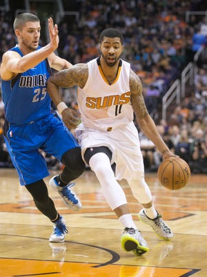 The Suns' Markieff Morris  drives to the basket as th Mavericks' Chandler Parsons defends during the second quarter of the NBA game at the US Airways Center in Phoenix on Tuesday, December 23, 2014.