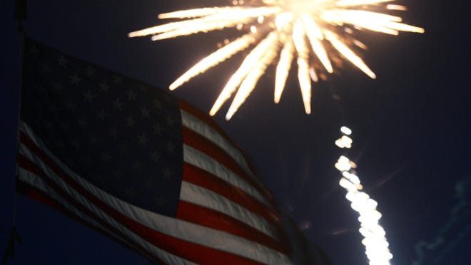 A rocket bursts behind an American flag during a fireworks display.