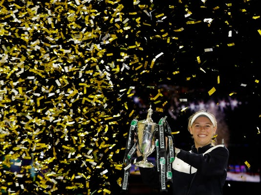 FILE - In this Sunday, Oct. 29, 2017, file photo, Caroline Wozniacki of Denmark lifts the winner's trophy after winning the singles final match against Venus Williams of the United States, at the WTA tennis tournament in Singapore. Wozniacki has become engaged again. The Danish tennis player says on Twitter that she accepted a marriage proposal from American basketball player David Lee (AP Photo/Yong Teck Lim, File)