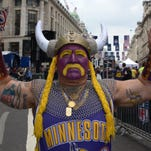 "Michael Hopson is dressed as ""Super Fan"" as he walks in Super Bowl Village, Friday, Feb. 3, 2012, in Indianapolis, Ind."