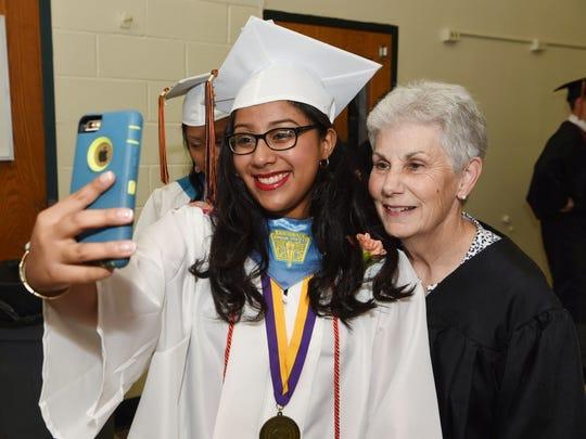 Graduating senior Alicia Rosado, left, takes a selfie