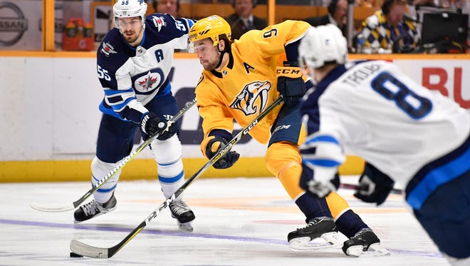 Predators left wing Filip Forsberg (9) moves the puck past Jets center Mark Scheifele (55) during the first period of Game 5 on Saturday.