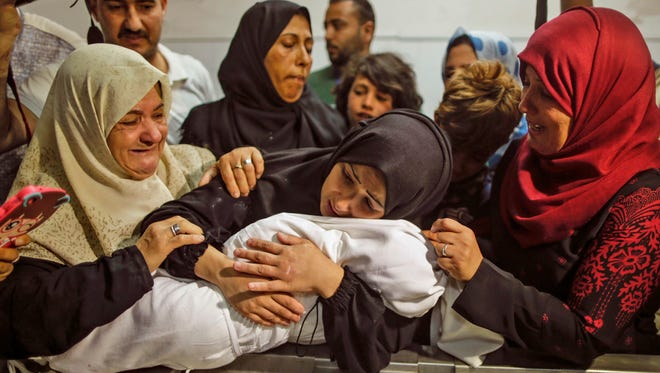 The mother of a Leila al-Ghandour (C), a Palestinian baby of 8 months who according to the Palestinian health ministry died of tear gas inhalation during clashes in East Gaza the previous day, holds her at the morgue of al-Shifa hospital in Gaza City on May 15, 2018Protests continued a day after Israeli forces killed 59 Palestinians during clashes and protests along the Gaza border against the U.S. Embassy opening in Jerusalem in the conflict's bloodiest day in years.