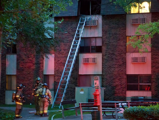 Lafayette firefighters wait at the base of a ladder after a fire at The Bluffs apartments sent a man to an area hospital Thursday, July 17, 2014, in Lafayette. The fire started in a third-story apartment.