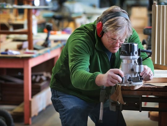 Carpenter Will McGown works on a chair made from an