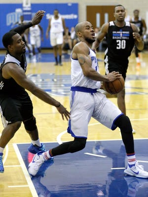 The Detroit Pistons' Lorenzo Brown, center, drives between the Orlando Magic White's Justin Dentmon, left, and Treveon Graham (30) during the second half of an NBA summer league game Friday, July 8, 2016, in Orlando. The Orlando Magic White won in overtime, 87-84.