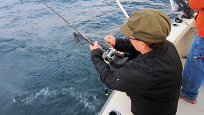 Wisconsinoutdoorfun.com blogger Marilynn Nash was the first to catch a fish during an August 2013 trip with Fishin' Magician's Charters of Algoma.