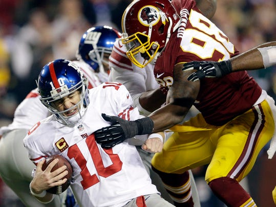 File-This Dec. 1, 2013, file photo shows New York Giants quarterback Eli Manning, left, being sacked by Washington Redskins outside linebacker Brian Orakpo, right, during the second half of an NFL football game  in Landover, Md.  If all goes according to plan, the Redskins should have a fierce pass rush featuring Hatcher, Orakpo, Ryan Kerrigan and draft pick Trent Murphy. (AP Photo/Patrick Semansky, File)