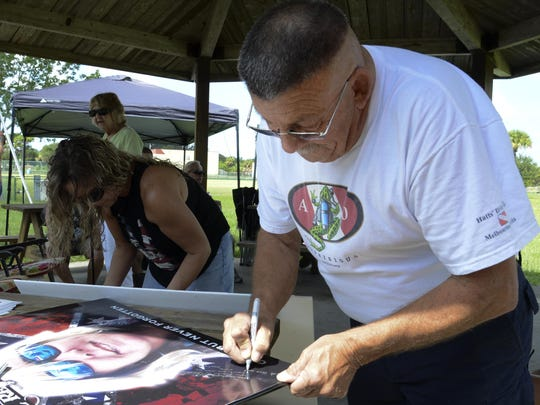 Joe Gianantonio signs a poster of Brandy Hall Saturday. Friends and family of missing firefighter Brandy Hall gathered in Malabar Community Park for a celebration of her life. Hall disappeared after leaving work 10 years ago.