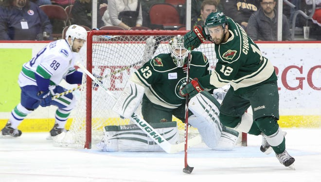 Wild defenseman Joel Chouinard clears the puck from infront of Iowa goalie John Curry in the first period on Sunday.