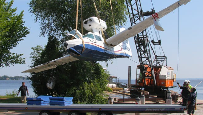 Crews unload the wreckage of a Lake Renegade from a Radtke Contractors barge about 10:30 a.m. Monday at the 24th Avenue boat ramp. Myers Contractors of Oshkosh took it away under police escort.