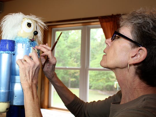 In this photo provided by the Richmond SPCA, Karen Gammon works in her studio in Richmond, Va., on a Muttcracker, a term she copyrighted which means nutcrackers with mutt heads, pivot joints with tails and paws for feet and hands. Gammons, 58, donates her art for auctions and gift stores.