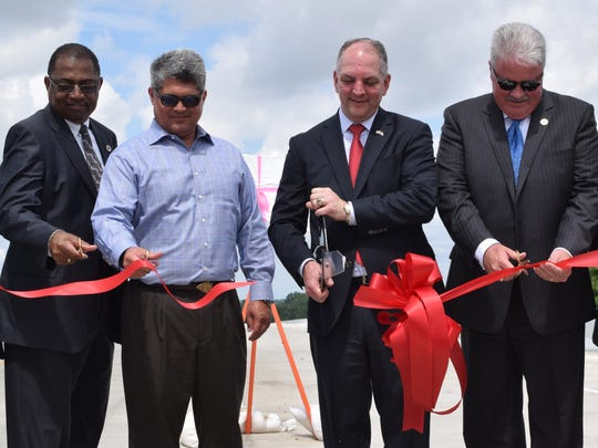 Gov. John Bel Edwards (second from right) uses giant scissors for a ribbon cutting to dedicate the Curtis-Coleman Memorial Bridge over the Red River on Tuesday. From left are state Rep. Jeff Hall, Alexandria Mayor Jacques Roy, Edwards and state Sen. Jay Luneau.