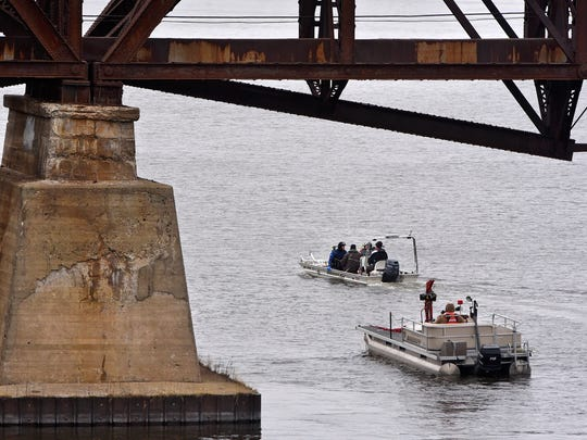 Divers return to a boat ramp after searching an area