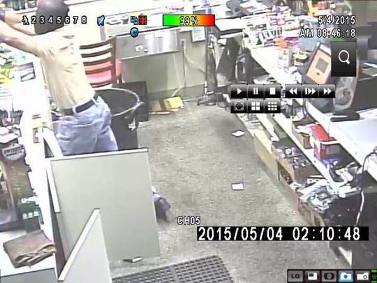 A masked burglar is seen stealing thousands of dollars worth of cigarettes, say police.
