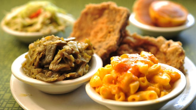 Fried pork chops, green beans, mac and cheese, fried cabbage and a plate of corn cakes at Dandgure's Cafteria