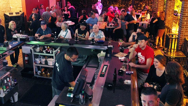 Patrons of BackStreets Sport Bar in Cape Coral sit out on the patio while watching basketball and singing karaoke on Saturday night.