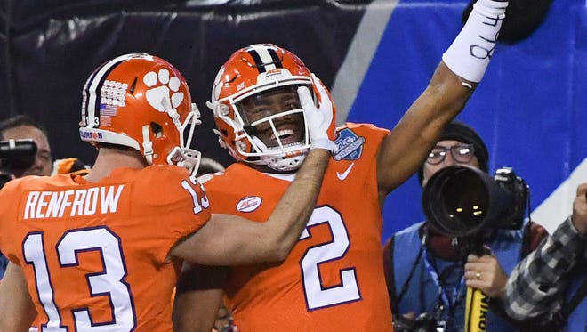 Clemson wide receiver Hunter Renfrow (13) hugs teammate quarterback Kelly Bryant(2) after he ran in a touchdown during the first quarter of the Dr.Pepper ACC football championship in Charlotte on Saturday.