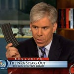 """This image made from video provided by NBC's """"Meet the Press"""" shows host David Gregory holding what he described as a high-capacity ammunition magazine during the taping of the Dec. 23, 2012 program."""
