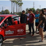 Young drivers check out a Kia as part of a program that provides defensive driving skills