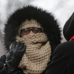 Valerie Coleman of Detroit covers her face while waiting for a bus on Woodward near Congress in downtown Detroit.