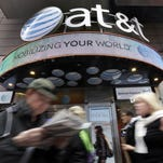 In this Oct. 21, 2014 photo, people pass an AT&T store in New York's Times Square. AT&T is being sued by the government over allegations it misled millions of smartphone customers who were promised unlimited data but had their Internet speeds cut by the company ó slowing their ability to open web pages or watch streaming video. (AP Photo/Richard Drew) ORG XMIT: NYBZ158