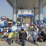 Mourners gather at a gas station in Houston on Aug. 29, 2015, to pay their respects at a makeshift memorial for Harris County Sheriff's Deputy Darren Goforth, who was shot and killed while filling his patrol car.