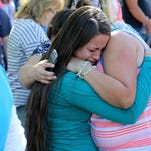 A woman is comforted as friends and family wait for students at the local fairgrounds after a shooting at Umpqua Community College in Roseburg, Ore., on Thursday, Oct. 1, 2015.