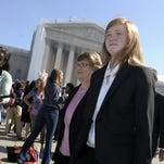 Abigail Fisher, who sued the University of Texas, walks outside the Supreme Court after her original case was heard three years ago.