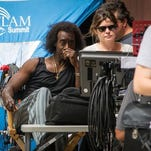 """Star-director Don Cheadle looks at a monitor between shots on """"Miles Ahead,"""" his movie about jazz great Miles Davis, on Seventh Street near Elm Street on July 7, the first day of filming."""