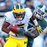 From 2014: Michigan Wolverines running back Justice Hayes (5) is ridden down by Michigan State Spartans linebacker Taiwan Jones (34) during the 2nd half of a game at Spartan Stadium. MSU won 35-11.