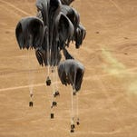 Airdropped supplies parachute down to a drop zone marked by warfighters on the ground in Afghanistan, in this 2010 photograph. The Air Force has performed airdrops many times and will drop aid to Syrian cities if asked, Secretary Deborah Lee James said Jan. 14.