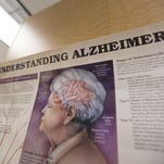 In this June 21, 2013 photograph, a poster with information about Alzheimer's Disease is posted on a shelf that holds books in the library at the Alzheimer's Association Headquarters in Chicago.