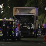 Police and rescue workers stand near a van that plowed through a crowd in the French Riviera town of Nice on Thursday, July 14.