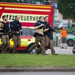 Police officers arrive at a shopping center where a shooting occurred today in Munich, southern Germany.