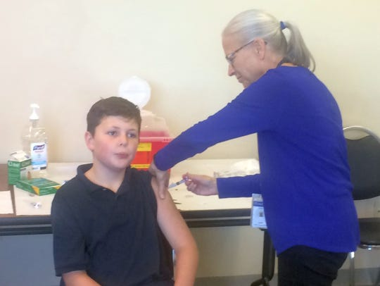 Cindy Trick, public health nurse with the Brown County Health Department, administers a flu shot to Henry Streckenbach, son of Brown County Executive Troy Streckenbach, during the kickoff of the county's 2016 Public Health Week at the department office in Green Bay.